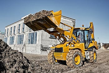 Hydrema 906F backhoe loader moving soil with it
